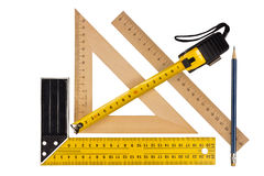 Measuring the angle and length. Metallic tool to measure right angle, triangle and wooden ruler, pencil and tape measure on a white background Royalty Free Stock Photos