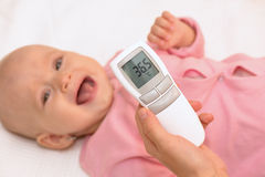 Measuring baby's temperature with contactless thermometer Stock Photo