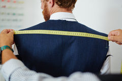 Measuring back. Clothier measuring back width of his client Stock Photos