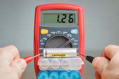 Measuring battery voltage with multimeter Stock Images