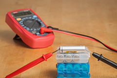 Measuring battery voltage with multimeter. Measuring battery voltage with digital multimeter on a workbench royalty free stock photography