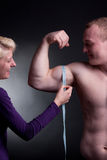 Measuring bicep. Bodybuilder with a measuring tape around his bicep Stock Photography