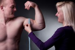 Measuring bicep. Bodybuilder with a measuring tape around his bicep Royalty Free Stock Photo