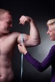 Measuring bicep. Bodybuilder with a measuring tape around his bicep Stock Image