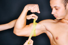 Measuring bicep. Bodybuilder with a measuring tape around his bicep Royalty Free Stock Photos