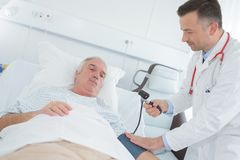 Measuring blood preassure senior sick patient. Measuring the blood preassure of a senior sick patient Stock Images