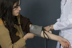 Measuring blood pressure. On young women Stock Photography