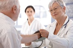 Measuring blood pressure. Senior female doctor measuring old man's blood pressure Royalty Free Stock Images