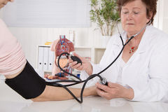 Measuring blood pressure with device instrument at doctor. Two w Stock Photos
