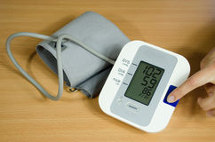 Measuring blood pressure finger on start button Royalty Free Stock Image