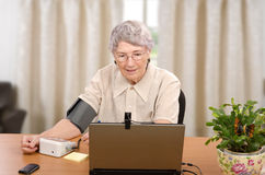 Measuring blood pressure in front of computer monitor Stock Image