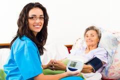 Measuring Blood Pressure. Kind nurse measuring elderly patient's blood pressure at home Royalty Free Stock Photography