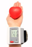 Measuring blood pressure and red heart in hand Royalty Free Stock Photo