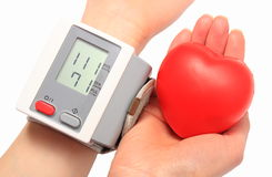 Measuring blood pressure and red heart in hand. Blood pressure monitor, medicine concept Stock Images
