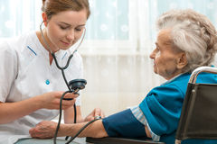 Measuring blood pressure of senior woman Stock Photo