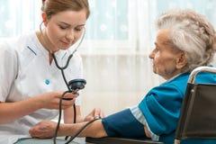 Measuring blood pressure of senior woman. Female nurse measuring blood pressure of senior woman Stock Photo