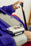 Measuring the blood pressure to an old man Stock Photos