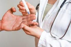 Measuring blood sugar on finger - diabetes concept Royalty Free Stock Image
