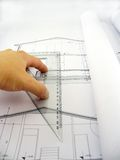 Measuring on blueprints. Hand measuring on blueprints Royalty Free Stock Photography