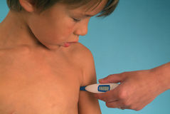 Measuring the body temperature of a child  Stock Photo