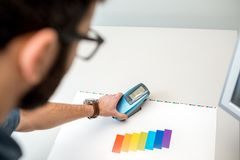 Measuring color with spectrometer tool. Measuring color on the paper print with spectrometer tool at the operating desk of the printing plant royalty free stock photography