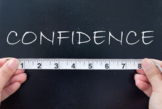 Measuring confidence. Tape measure aligned against the word confidence handwritten on a chalkboard royalty free stock photo