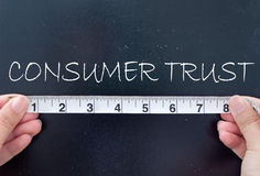 Measuring consumer trust. Hands measuring consumer trust on a chalkboard stock photography