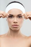 Measuring the correct proportion of eyebrows. Closeup portrait of young attractive woman being measured the correct proportion of eyebrows. Plastic surgery royalty free stock photo