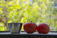 A measuring cup and two tomatoes. A steel measuring cup and two ripe red Tomatoes on a cutting board, kitchen utensil and vegetables towards a green fresh bokeh stock photos