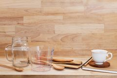 Measuring cup and wooden spoon, cooking supplies on wood backgro Stock Image