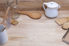measuring cup and wooden spoon, cooking supplies on wood backgro Royalty Free Stock Photo