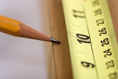 Measuring for the cut 2. A woodworker measures the mark for his cut Stock Image