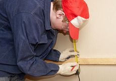 Measuring the distance. The worker measures the distance and puts a mark Stock Image