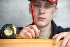 Measuring the distance. The worker measures the distance and puts a mark Stock Images
