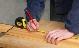 Measuring the distance. The worker measures the distance and puts a mark Royalty Free Stock Photography