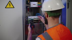 measuring electrical voltage by multimeter, electrician is looking for breakdown