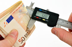 Measuring euro banknotes with vernier caliper Royalty Free Stock Images
