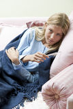 Measuring fever. Young woman with temperature and flu Stock Image