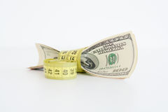 Measuring the financial success. Dollar bills tied up with measuring tape suggesting measuring the financial success Stock Photos
