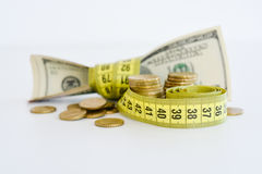Measuring the financial success. Dollar bills tied up with measuring tape suggesting measuring the financial success Royalty Free Stock Photography