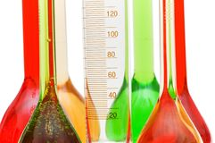 Measuring glass and coloured retorts on white royalty free stock images