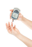 Measuring glucose level blood test using mini glucometer Royalty Free Stock Photo