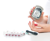 Measuring glucose level blood test using mini glucometer Stock Image