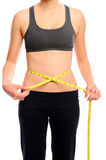 Measuring her waist; diet success. Slim fit woman using a tape measure to see how much weight she has lost on her diet Royalty Free Stock Photos