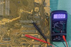 Measuring instrument multimeter with yellow-brown printed circuit board. Multimeter probes on a printed circuit board is next to a multimeter stock photo