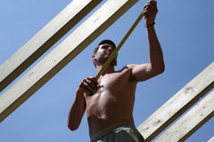 Measuring the Length. A consturction worker measures a roof beam stock images