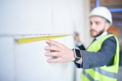 Measuring length. Contemporary enginer in workwear measuring length of concrete wall of unfinished construction with yellow tape stock photo