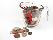 Measuring Money. One cup of American coins in a glass measuring cup royalty free stock photos