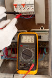 Measuring with multimeter. Electrician checking fuse box with a digital multimeter stock photos