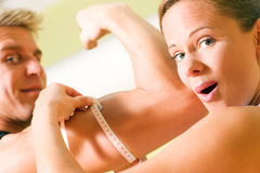 Measuring muscles. Woman measuring rather impressive circumference of arm with muscles of her guy Stock Image